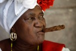 Street entertainer and fortune teller ¨Juana La Cubana¨ holds a cigar in her mouth as she waits for tourists in Havana, Cuba, Sunday, May 24, 2015. Juana is 72 years old and has worked in the Cathedral square in Old Havana for 28 years. (AP Photo/Desmond Boylan)
