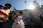 Carmen Gonzalez (C) walks with her mother Marlen (L) for a photo session in the old quarters of Havana, for her quinceanera (coming-out for 15-year-olds) celebration, January 14, 2013. As nearly all Cuban girls dream of having a quinceanera, the industry that moves around that dream is large, with clients ranging from wealthy Cuban-Americans who travel back to the island to sponsor lavish parties, to regular Cubans who save a few hundred dollars over several years from their monthly $18 state wage. Picture taken January 14, 2013. REUTERS/Desmond Boylan (CUBA)