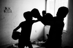 Two young boy fights with boxing gloves inside of their living place. Dhaka, Bangladesh.