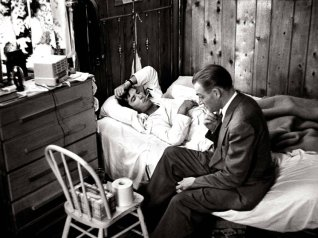 """El Dr. Ceriani se sienta a la cabecera de un paciente mientras evalúa los síntomas de la gripe durante una llamada domiciliaria. Cuando Smith comenzó """"Country Doctor"""", tiró por un período de tiempo sin película en la cámara, para ayudar a Ceriani a acostumbrarse a su presencia sin desperdiciar la preciada película."""