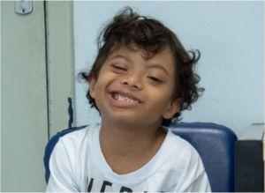 Menino com síndrome de down sorri para a foto