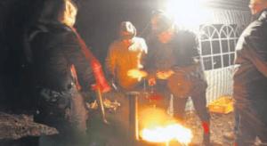 Nachlegen: Damit das Feuer in der Tonne auch ordentlich brennt, haben die Organisatoren reichlich Holz parat.