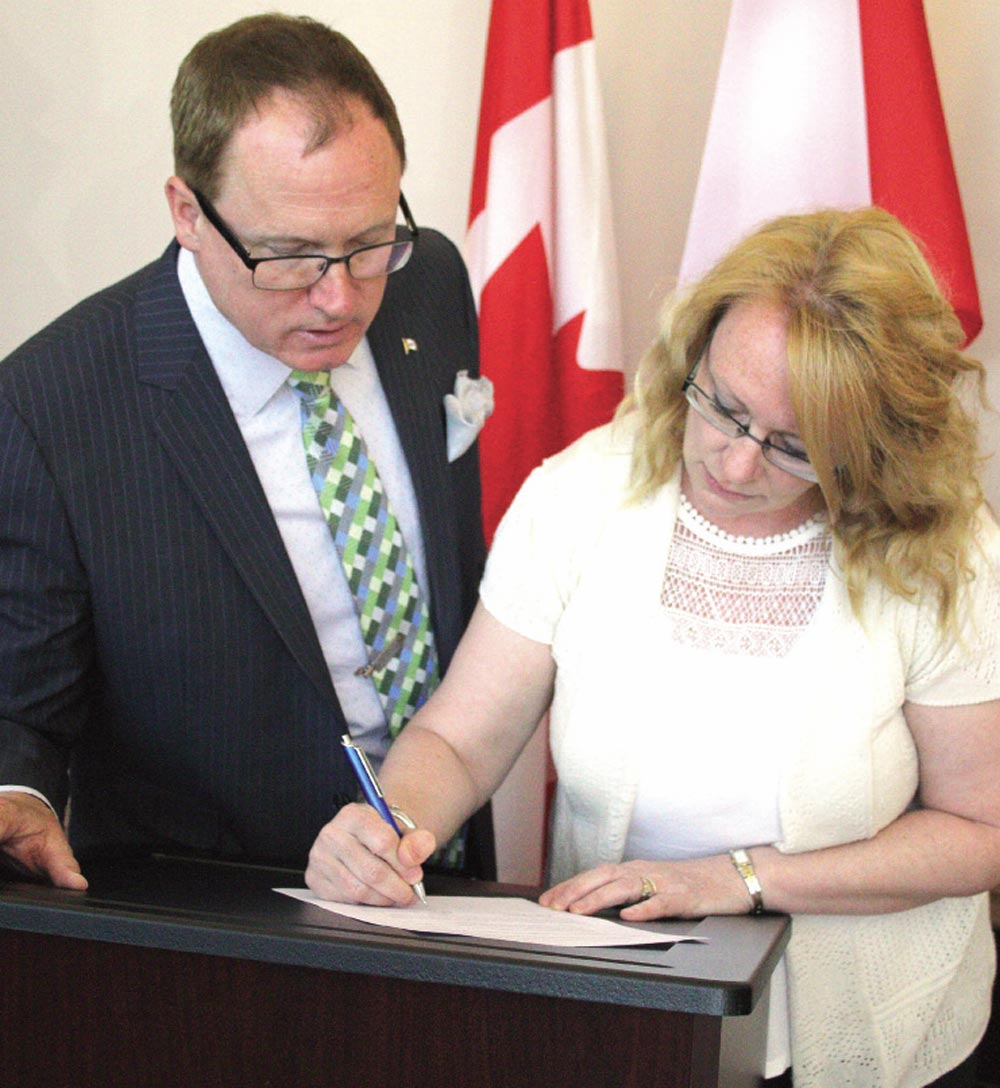Oshawa MP Colin Carrie looks on as Lisa Freeman officially adds her name to the petition she launched. Freeman is calling on the federal government to be more honest and transparent in the conviction certificates it releases after the man who was convicted of killing her father in 1991 was permitted escorted absences from jail in 2012, four years before he was eligible to apply for parole.