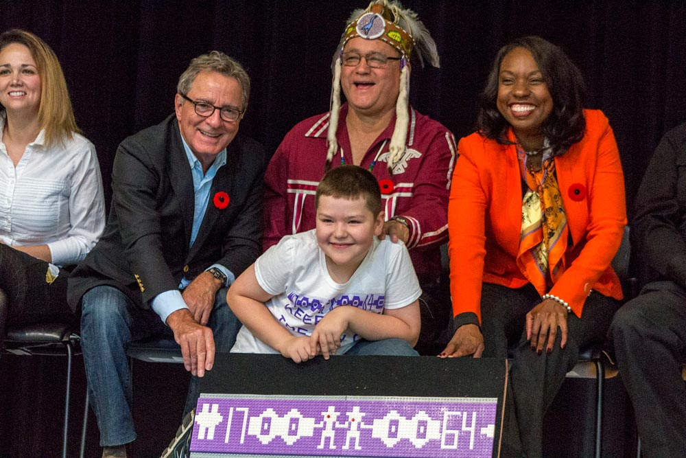 David Zimmer, the province's minister of indigenous relations and reconsiliation; Patrick Madahbee, the grand council chief for the Anishinabek Nation; and Mitzie Hunter, the province's education minister, join Alexander Hebert and his replica of the wampum belt made for the Treaty of Niagara of 1764,