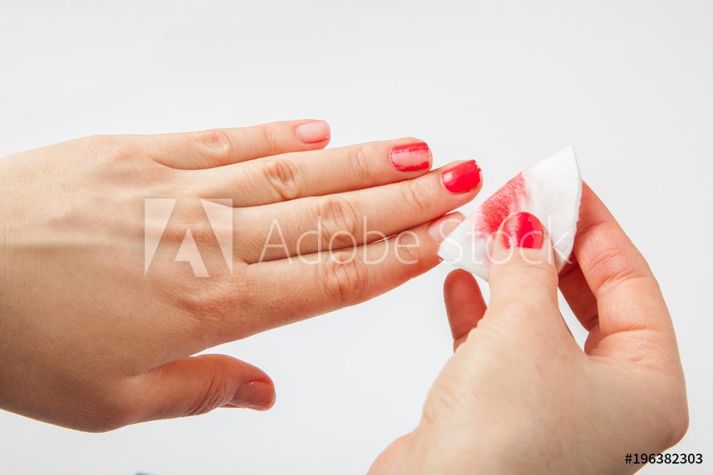 빨간 매니큐어를 바른 사람이 솜에 아세톤을 묻혀서 손톱에 발라져있는 빨간 메니큐어를 지우고있다,