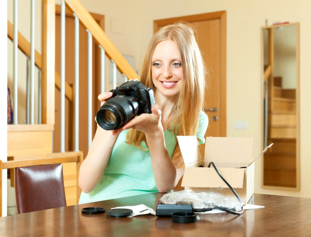 금발머리이며 민트색 옷을 입은 여성이 양손으로 카메라를 들고 응시하는 모습의 사진