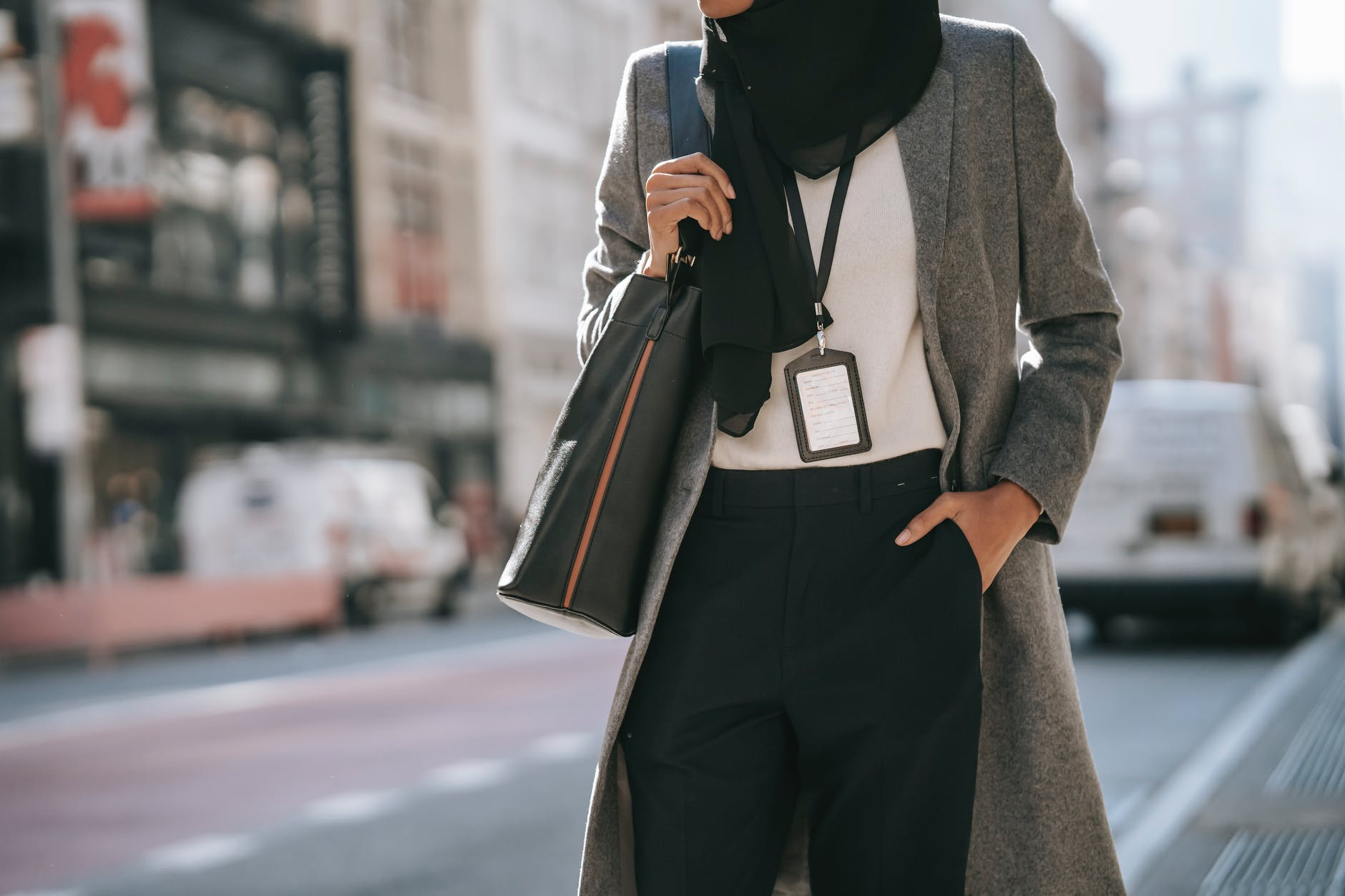 trendy muslim businesswoman standing on city street