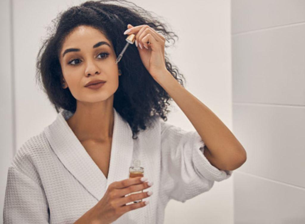 건조한 피부 관리, 한 여자가 화장실에서 얼굴에 페이스오일 한 방울을 떨어트리고 있다