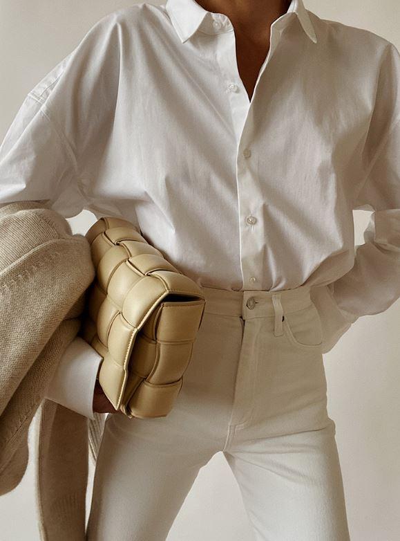 한 여자가 화이트 셔츠에 화이트팬츠 베이지 자켓 옐로우톤의 가방으로 스타일링했다