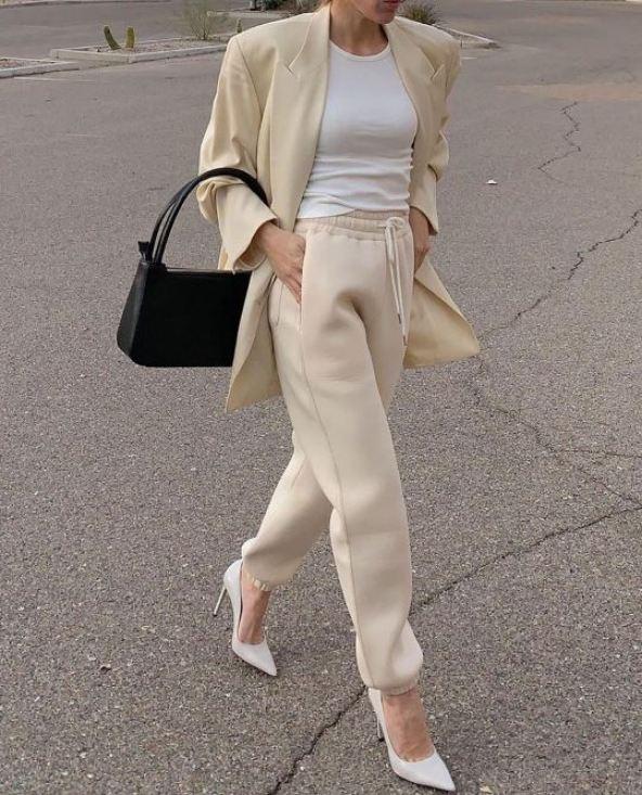 타이트한 흰색 티셔츠와 베이지색 조거팬츠, 옐로우 재킷을 입고 흰 구두를 신은 패셔너블한 여자