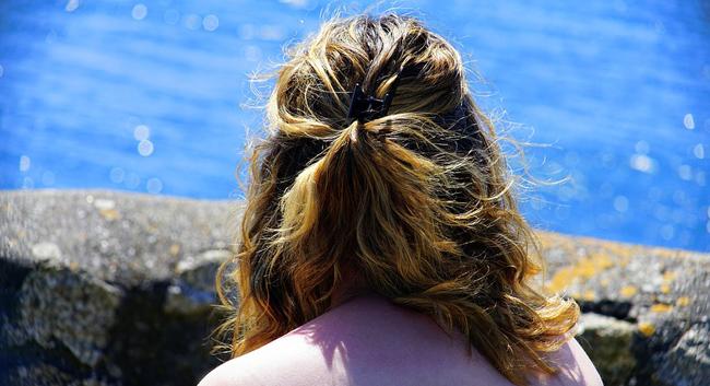 한 여성의 뒷모습이 보인다. 머리카락에 바세린을 발라주면 보다 윤기나고 차분한 머릿결을 연출할 수 있다.
