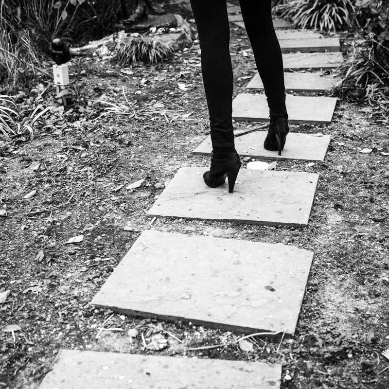 A woman stands the pathway surrounding Ghandi's statue.