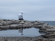 Photo of Person Sitting on Rocks