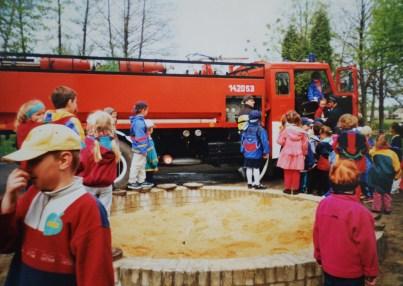 Ciężki samochód gaśniczy stoi na przedszkolnym placu otoczony dziećmi