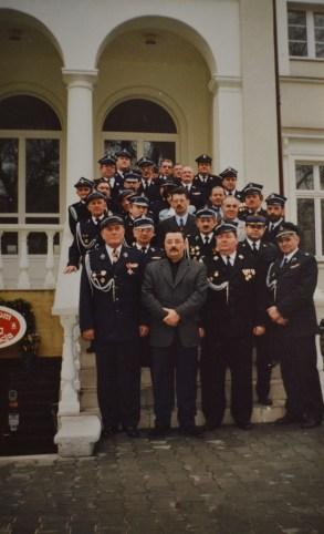 Druhowie OSP z całego powiatu w mundurach galowych przed białym domkiem w Mikołowie