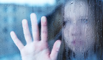 Anxious and depressed young woman at the window in the rain