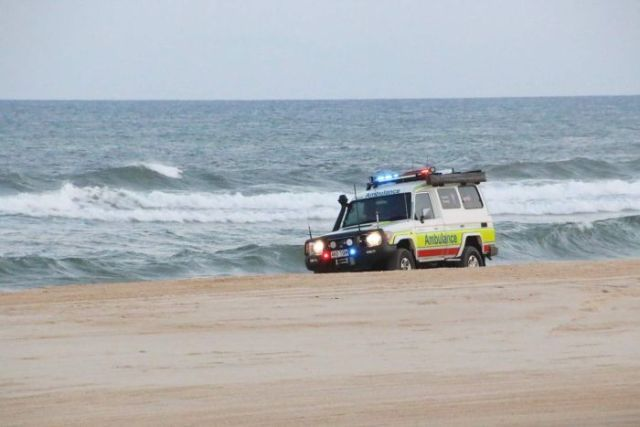 Ambulance four-wheel-drive vehicle driving on beach with surf in background on Fraser Island.