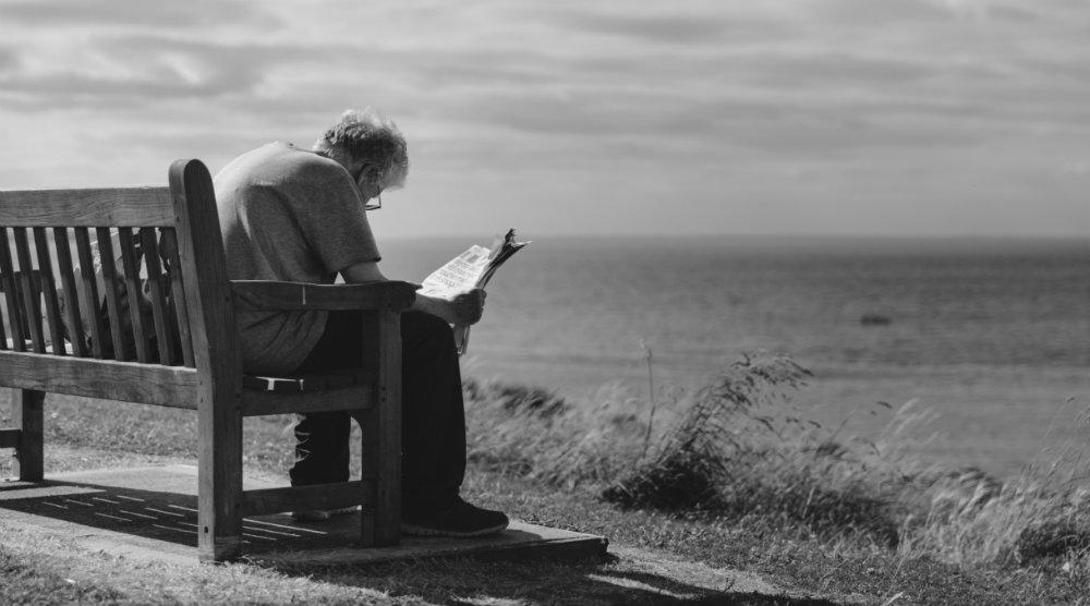 Photo d'un homme assis sur un banc au bord de la plage, lisant un journal penché vers l'avant. Sa posture est-elle bonne ou mauvaise ? Quel effet aurait le t-shirt Percko sur sa posture, ses douleurs ?