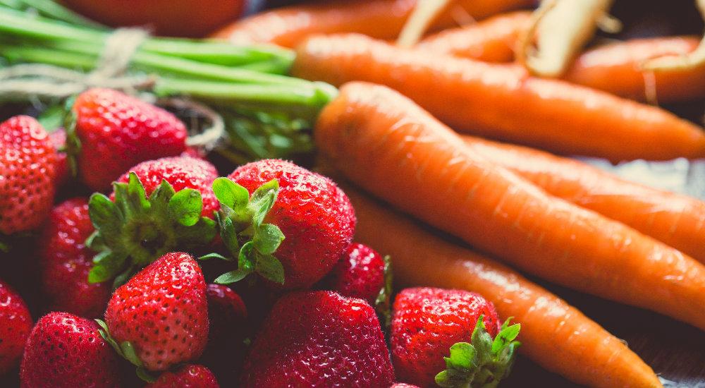 Photo de fruits et légumes (fraise et carotte). Les fruits et légumes sont riches en prébiotioques grâce aux fibres qu'ils contiennent. Ce sont des aliments qui équilibrent le microbiote.