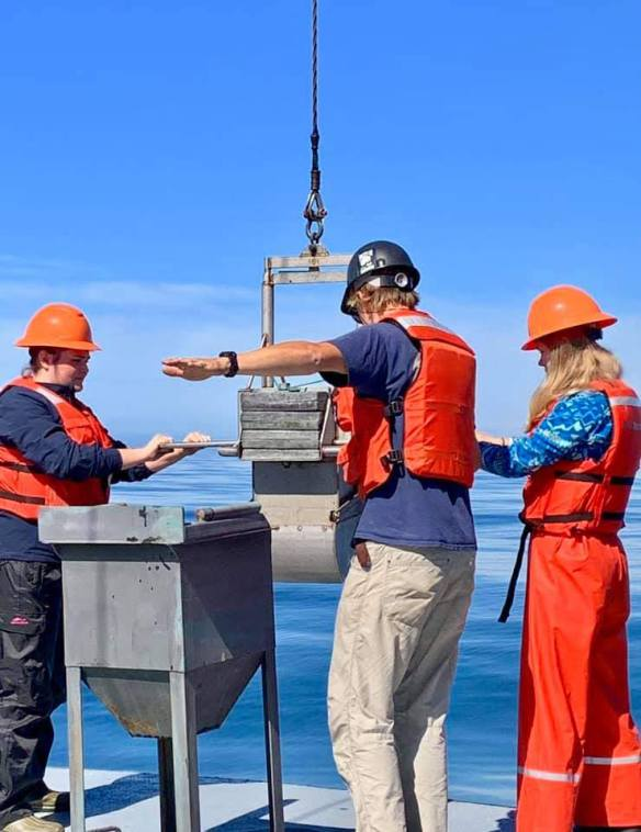 three people bring the box core sample on board the ship