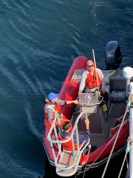 three people in a red rigid hull inflatable boat