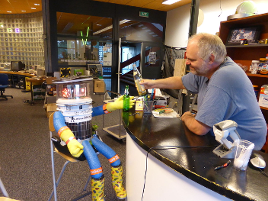 Hitchbot the robot sitting at a bar and a man hands him a bottle