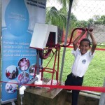 Small boy demonstrating Public Health water filter pump