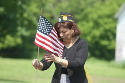 Donna Kestner, the county's director of the Veterans Service Agency, places a flag at the end of the ceremony. Photo by Harrison Wilde.