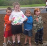 Pictured are Parker Ellis, Makayla Ellis, Cadon James, and Dawson Krause holding the stone that was placed at the site with the children's handprints on it.