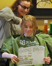 Meghan Parras holds up a sign displaying who she is shaving for.