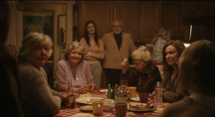Diane sentada numa mesa de jantar com um grupo de senhoras