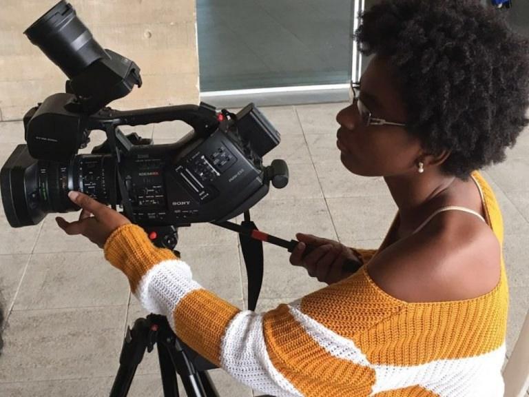 Mulher preta com câmera nas mãos