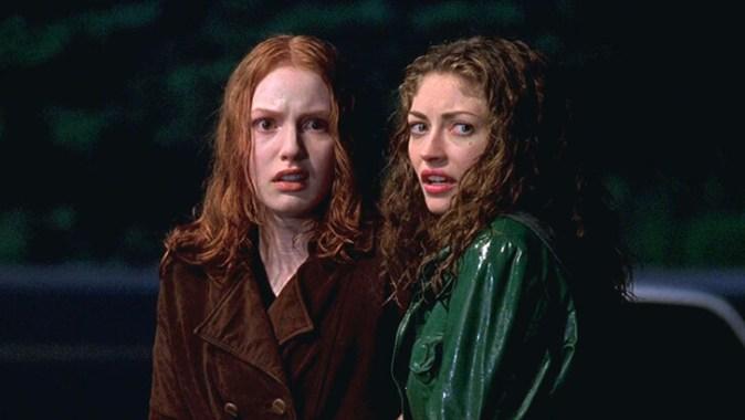 Duas moças, uma ruiva e outra morena, com o cabelo molhado na chuva