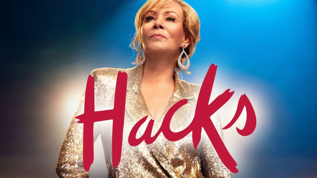 """Na imagem temos a protagonista, Deborah Vance, em um terno dourado e a logo da série, """"Hacks"""", em vermelho."""