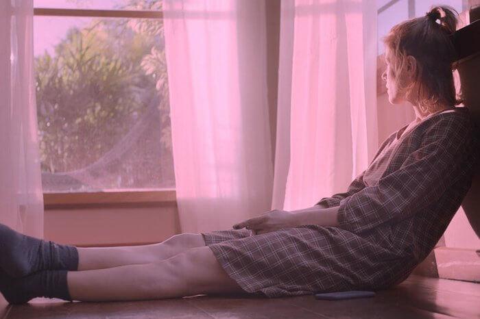 Mulher loira sentada numa janela olhando para o horizonte