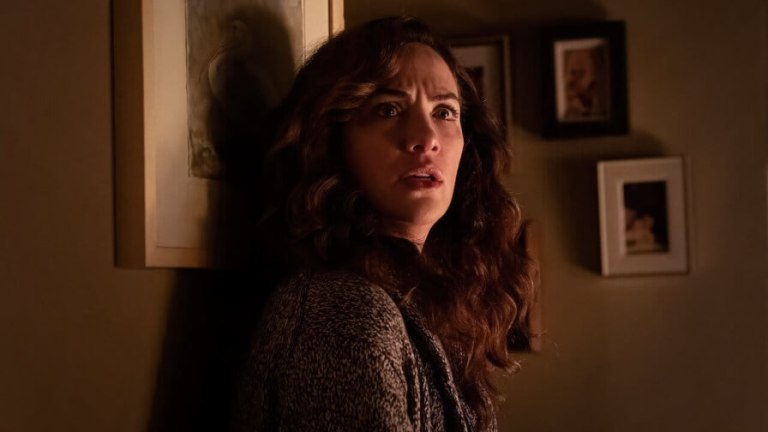 Em imagem de A Missa da Meia-Noite, uma mulher morena olha confusa para alguém enquanto está encostada numa parede com fotos
