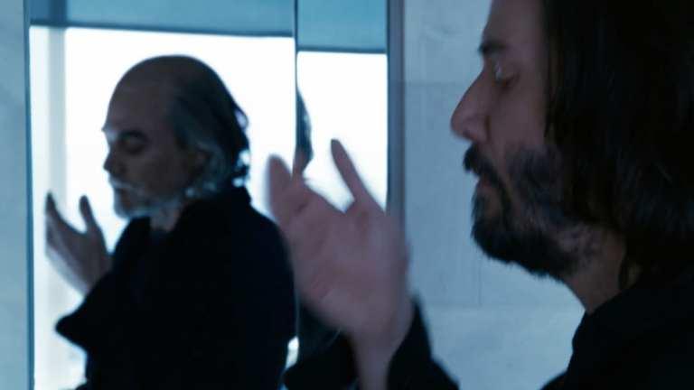 Homem de de preto com olhos fechados, erguendo às mãos para cima, ele esta diante de um espelho, no seu reflexo aparece um homem bem mais velho que ele, como as mesma roupas, mas mais grisalho