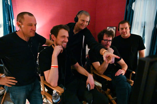 Homens vestidos de blusa preta e calça jens, 2 sentados em 3 em pé, parecem ser cinegrafistas