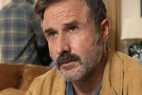 Homem grisalho com bigodes pensativo de jaqueta bege
