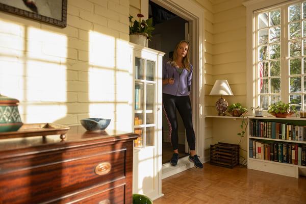 Uma sala de estar bem ampla e iluminada pela luz solar, há uma mulher loira na porta adentrando à sala com certo receio