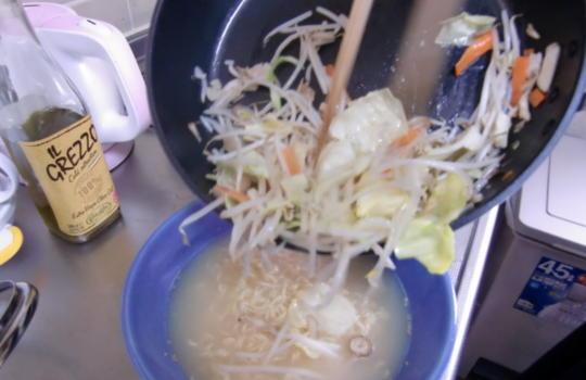 炒めた野菜をどんぶりに加えている画像
