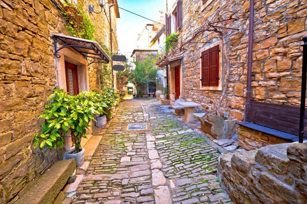 A narrow, cobblestone street lined with stone homes in Groznjan, Croatia