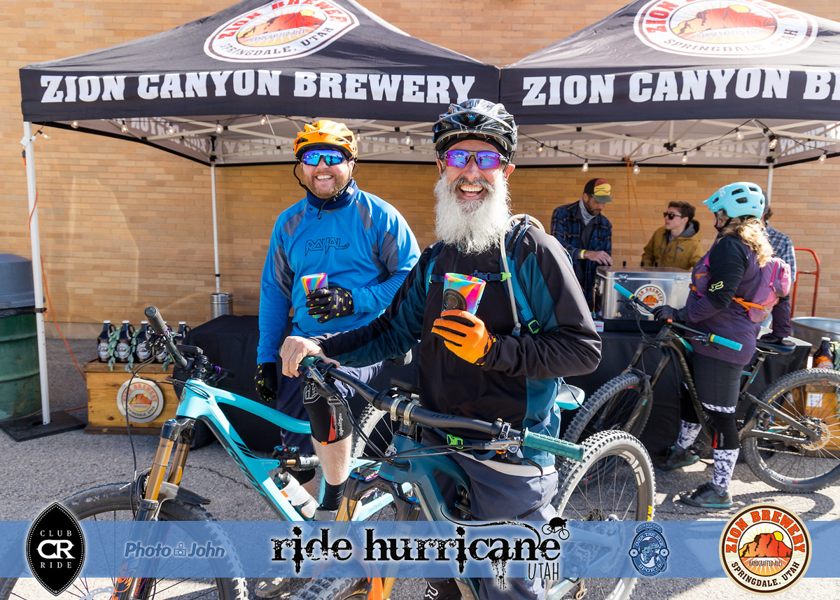Smiling mountain bikers with beers and Zion Canyon Brewery tent in the background