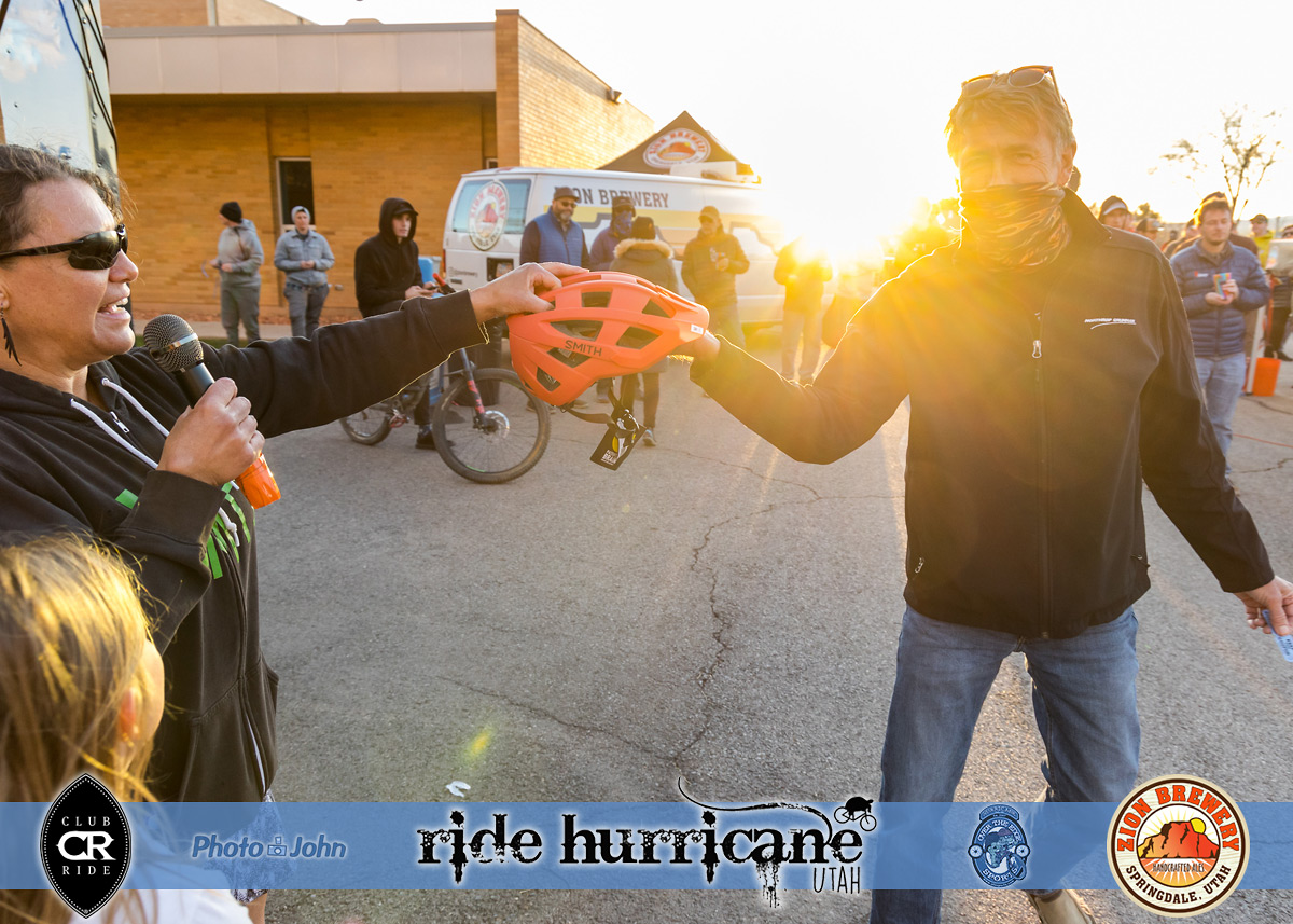 A woman handing a bike helmet to a raffle winner
