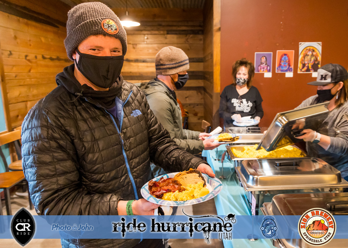 Man in a mask and puffy jacket with a plate of breakfast food.