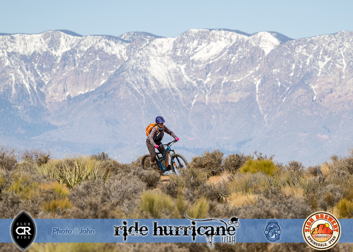 A lone mountain biker riding through sage brush with snowy mountains in the background.