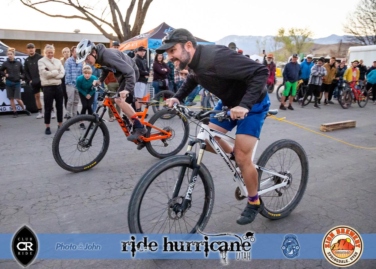 Two men on mountain bikes racing bikes pulling logs.