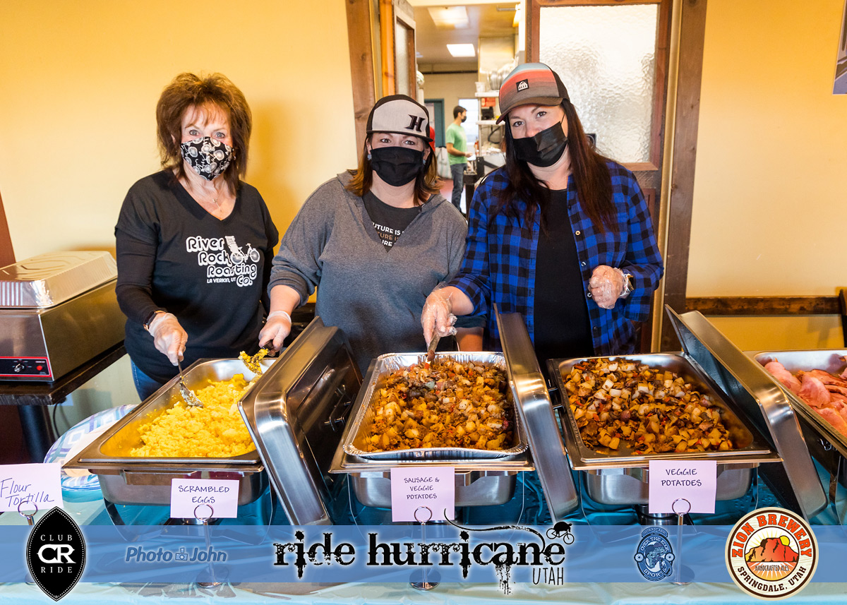 Three women wearing masks with trays of breakfast food.