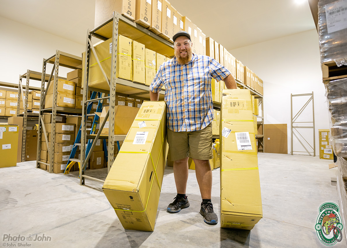 A smiling man in a warehouse holding two large mountain bike shipping boxes.