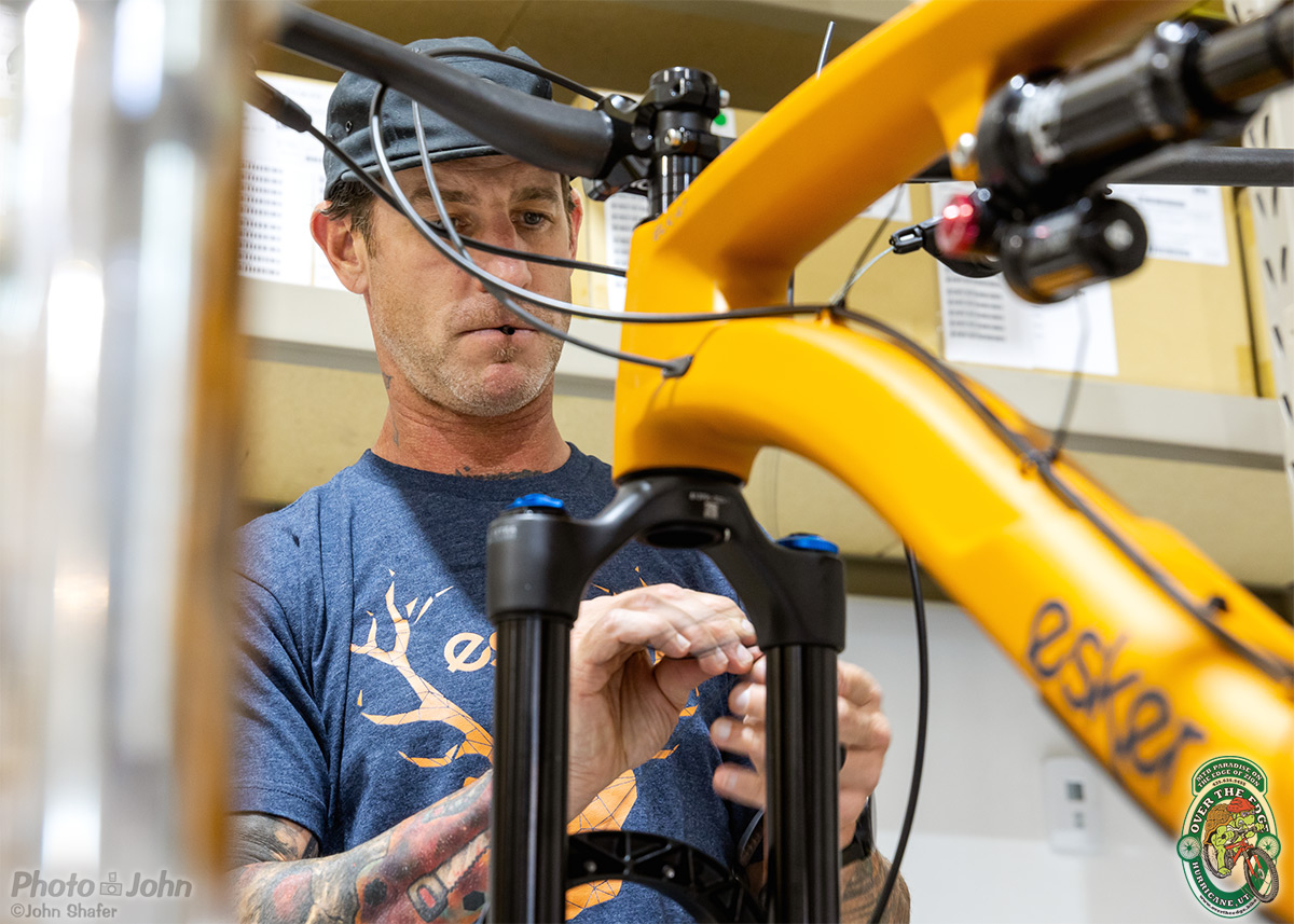 Man, seen through an orange mountain bike, with a part in his mouth, assembling a bike part in his hands.